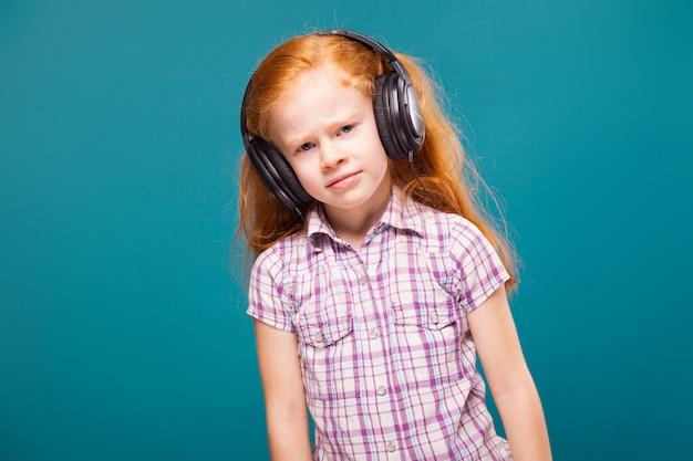 Linda, fofa menina de camisa quadriculada e fones de ouvido com longos cabelos vermelhos ouvir musik