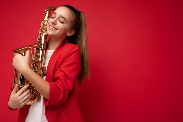 Linda fofa positiva sorridente morena pequena adolescente feminina vestindo uma jaqueta vermelha da moda em pé isolado sobre a parede de fundo vermelho segurando o saxofone e sonhando com olhos fechados