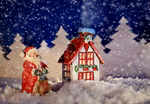 Linda foto de conto de fadas de natal de uma casa e o papai noel na noite de inverno na neve