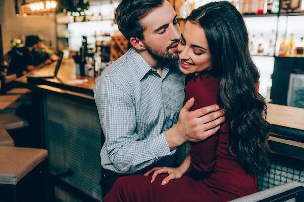 Linda foto de homem bonito e mulher bonita sentada muito juntos. ele está segurando-a nas mãos dela e tentando beijá-la. ela está sorrindo e não se importa com isso.