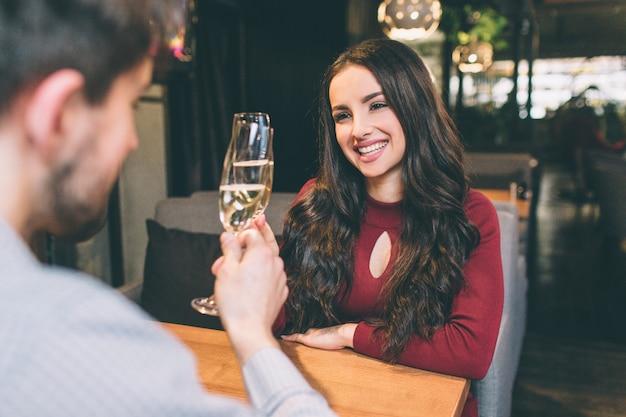 Linda foto do lindo casal sentado à mesa e bebendo champanhe. eles estão comemorando o aniversário de seus relacionamentos. ambos estão felizes com isso.