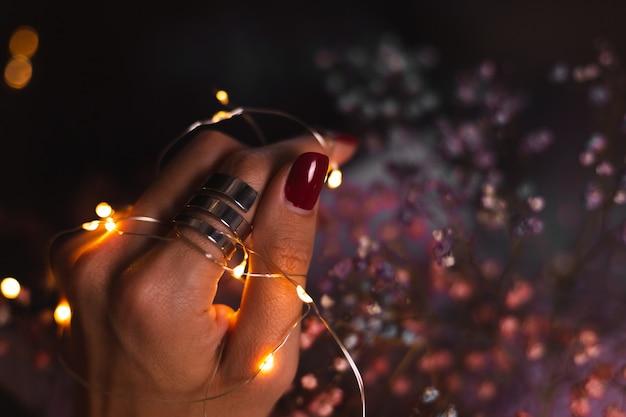 Linda foto escura dos dedos das mãos de uma mulher com um grande anel de prata de flores e luzes brilhantes Foto gratuita