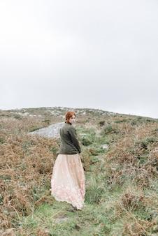 Linda foto vertical de uma mulher ruiva com pele totalmente branca em um atraente vestido claro