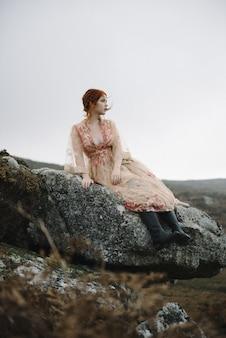 Linda foto vertical de uma mulher ruiva com pele totalmente branca em um lindo vestido rosa