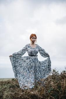 Linda foto vertical de uma mulher ruiva com pele totalmente branca em um vestido azul claro