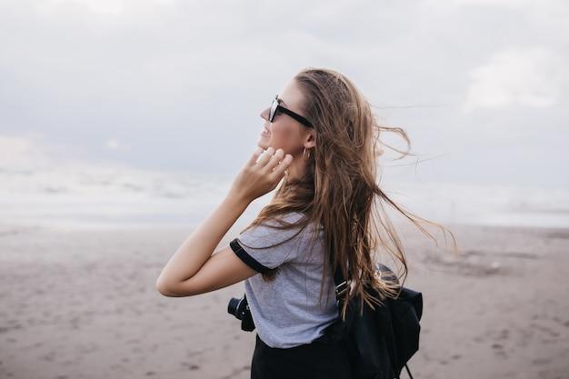 Linda fotógrafa em t-shirt cinza, olhando para o céu nublado. retrato ao ar livre de uma romântica menina morena com câmera se divertindo na praia em um dia frio.