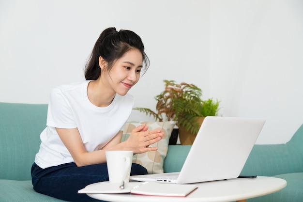 Linda freelancer feminina falando em videoconferência online com o laptop em casa