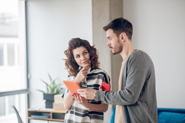 Linda funcionária com um computador tablet, olhando para seu colega sério e fofo com um smartphone