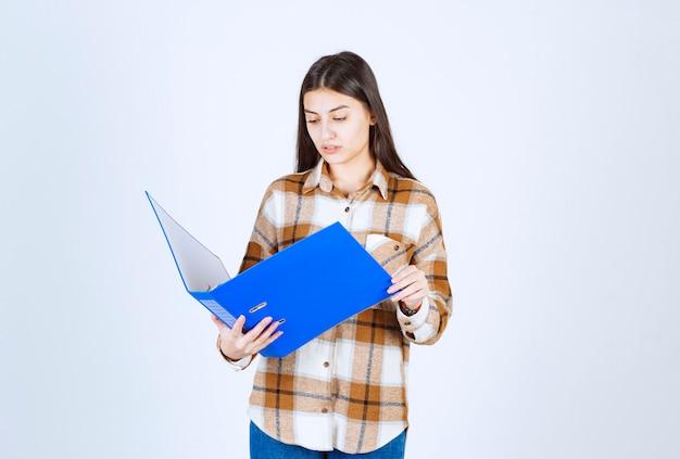 Linda funcionária lendo documentos importantes na parede branca.