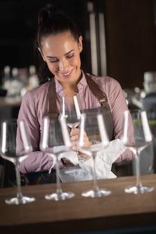 Linda garçonete preparando taças de vinho em um bar, sorrindo.