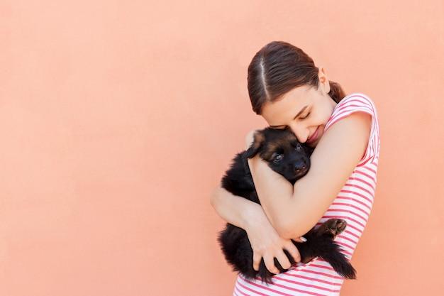Linda garota abraçando apertado seu filhote de cachorro pequeno bonito