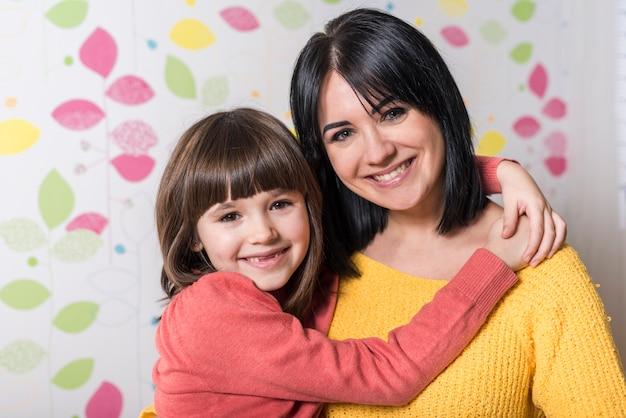 Linda garota abraçando mãe feliz
