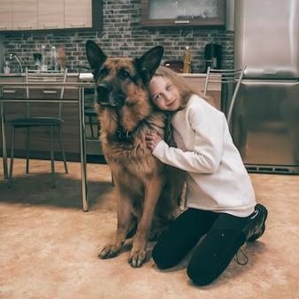 Linda garota abraçando seu pastor alemão de estimação na cozinha de casa. amados animais de estimação