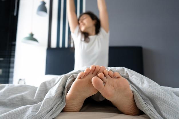Linda garota acorda de bom humor em um apartamento elegante. vista dos pés