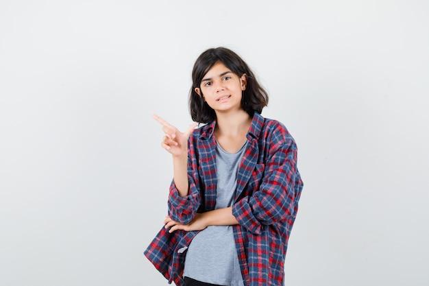 Linda garota adolescente apontando para o canto superior esquerdo em uma camisa e olhando confiante, vista frontal.