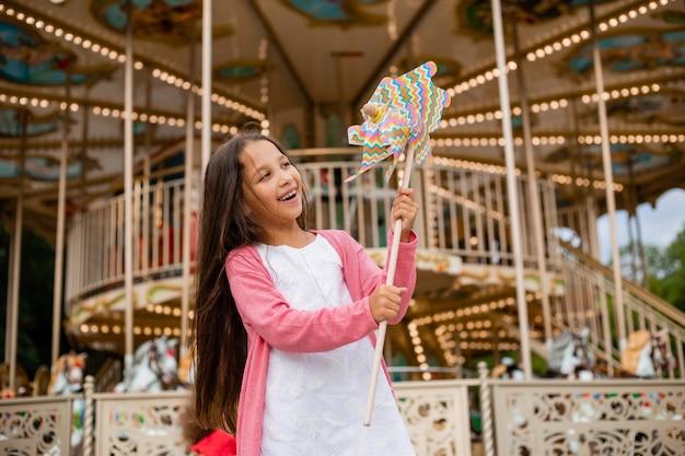 Linda garota adolescente brincando perto do carrossel na brisa de brinquedo