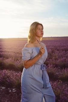 Linda garota adolescente caminhando em um campo de lavanda