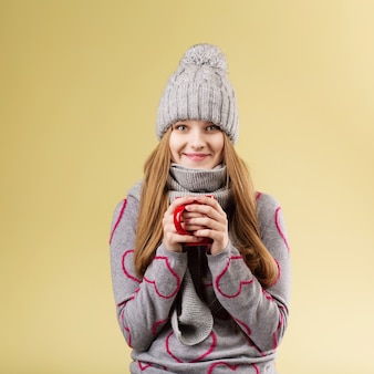 Linda garota adolescente com boné de lã cinza e lenço aquecendo as mãos em uma xícara de chá quente