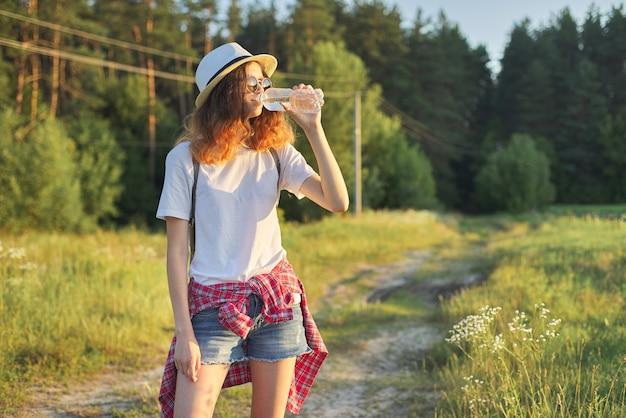 Linda garota adolescente com chapéu e mochila com garrafa de água doce num dia quente de verão