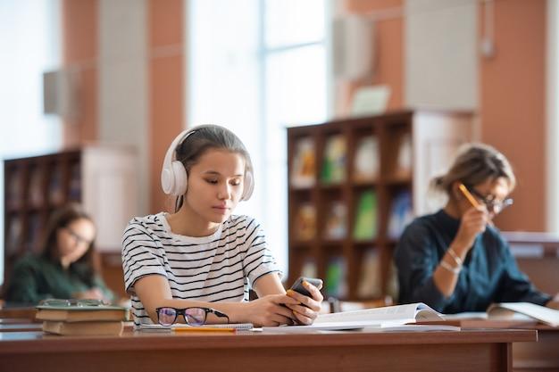 Linda garota adolescente com fones de ouvido e pulôver casual rolando no smartphone na biblioteca enquanto se prepara para o seminário