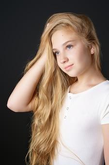 Linda garota adolescente com longos cabelos loiros em uma camiseta branca
