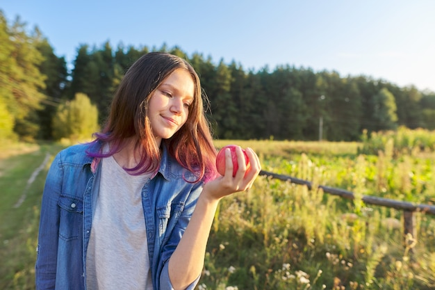 Linda garota adolescente com maçã vermelha, jovem feliz na natureza, fundo de paisagem do pôr do sol cênico, espaço de cópia, conceito de comida natural saudável