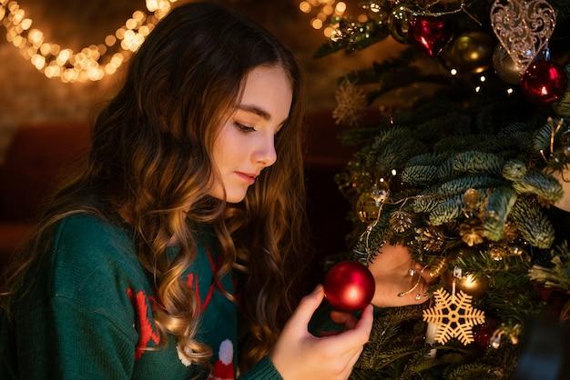 Linda garota adolescente decora a árvore de natal com bolas vermelhas no suéter verde com veados aconchegantes e mágicos.