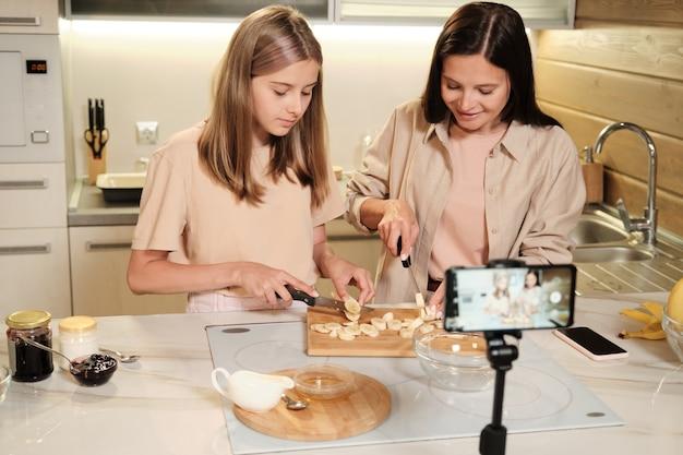 Linda garota adolescente e a mãe dela cortando bananas frescas na placa de madeira perto da mesa durante a aula de mestre em casa na frente da câmera do smartphone