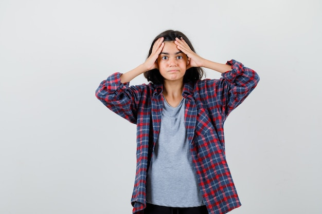 Linda garota adolescente em camisa de mãos dadas na cabeça e olhando confusa, vista frontal.