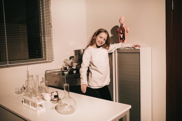 Linda garota adolescente em pé perto da mesa do laboratório. o conceito de um hobby