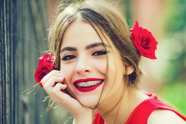 Linda garota adolescente espanhola com lábios vermelhos e rosas no cabelo. cara feliz.