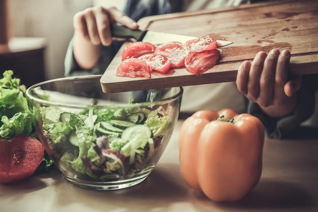 Linda garota adolescente está adicionando tomates na tigela.