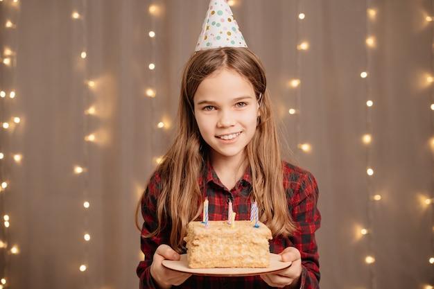 Linda garota adolescente feliz com bolo de aniversário.