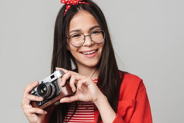 Linda garota adolescente feliz vestindo roupa casual em pé, isolada na parede cinza, segurando uma câmera de retrato