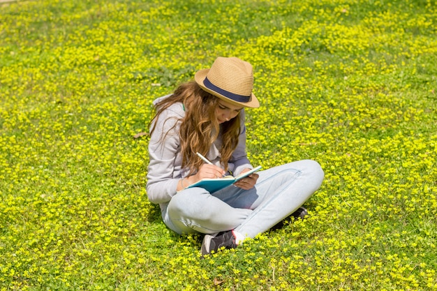 Linda garota adolescente lendo um livro sobre um prado verde.