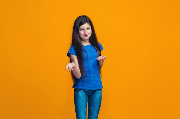 Linda garota adolescente parecendo surpresa e perplexa isolada em laranja