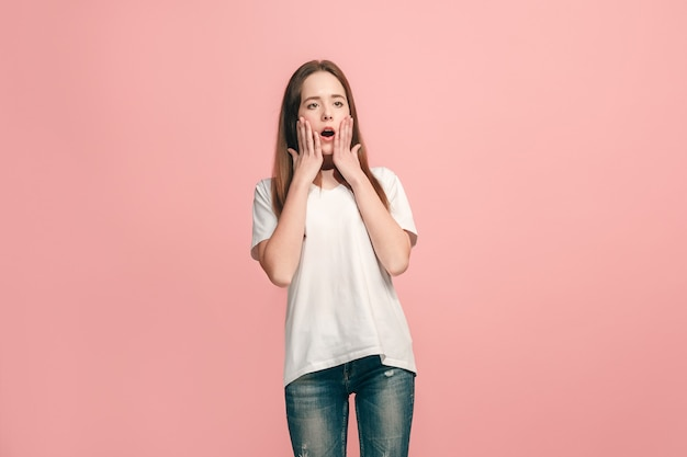 Linda garota adolescente parecendo surpresa isolada em uma parede rosa