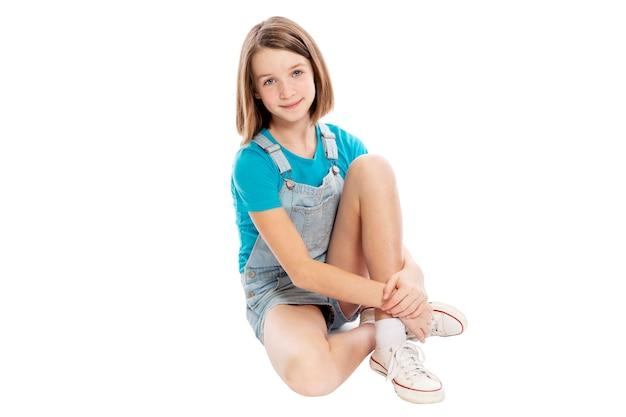 Linda garota adolescente sentado. isolado em um fundo branco.