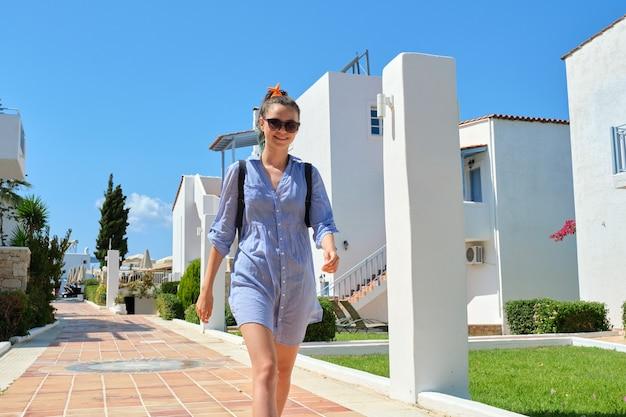 Linda garota adolescente sorridente andando, dia ensolarado de verão na vila de resort, edifícios brancos no hotel spa. lazer, recreação, turismo, estilo de vida de jovens, adolescentes