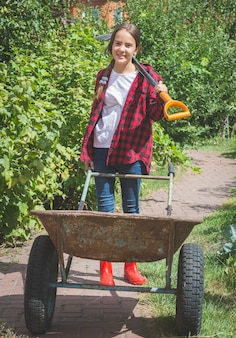 Linda garota adolescente sorridente em galochas trabalhando no jardim