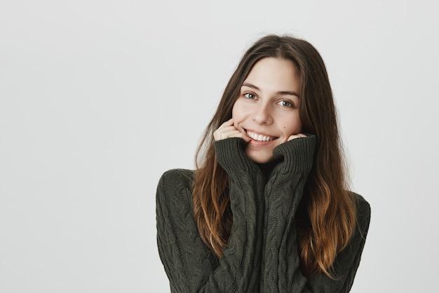 Linda garota adorável camisola, sorrindo câmera boba e tocar as bochechas