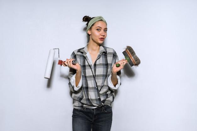 Linda garota adorável fazendo reparos em seu apartamento, segurando um pincel e rolo para pintar as paredes