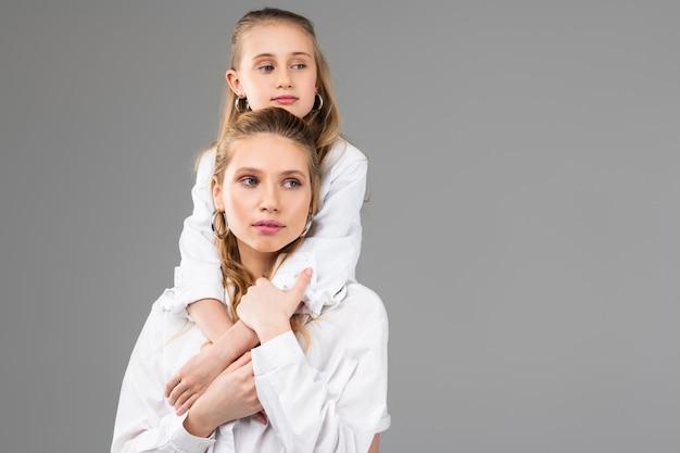 Linda garota adulta atenciosa com brincos de prata cobrindo as mãos da irmã enquanto ela fica para trás