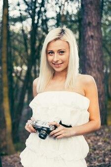 Linda garota adulta com câmera fotográfica retrô