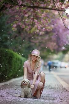 Linda garota adulta com um cão de raça pequena em roupas cor de rosa