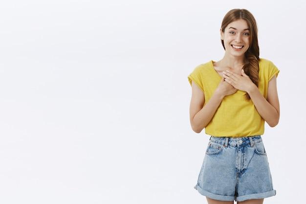 Linda garota adulta, simpática e fofa, com camiseta amarela e shorts segurando as palmas das mãos no peito e sorrindo, sentindo-se grata e agradecida