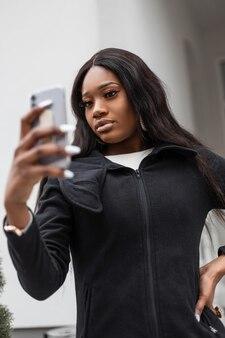 Linda garota africana com smartphone tirando selfie na cidade