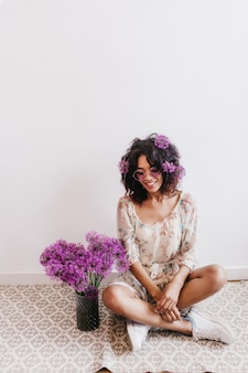 Linda garota africana com um lindo vestido de verão sentada perto de um vaso de alliums. retrato interior da senhora negra morena relaxando em casa.