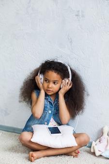 Linda garota africana em casa, ouvindo música em fones de ouvido brancos grandes