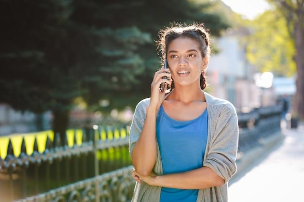 Linda garota africana falando no telefone no fundo da natureza